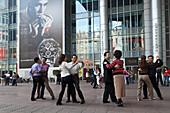 People dancing under the arcades of a building, Nanjing Road, Shanghai, China, Asia