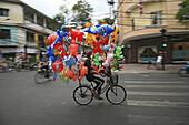 Balloon vendor on a bike during Tet festival, Saigon, Ho Chi Minh City, Vietnam, Asia