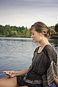 Young woman listening to music at lake Starnberg, Bavaria, Germany