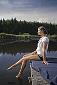 Junge Frau sitzt auf einem Steg am Starnberger See, hört Musik, Bayern, Deutschland