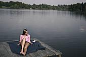 Junge Frau liegt auf einem Steg und liest ein Buch, Starnberger See, Bayern, Deutschland