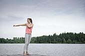 Junge Frau beim Stretching auf einem Steg am Starnberger See, Bayern, Deutschland