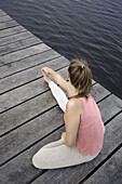Young woman stretching on a jetty at lake Starnberg, Bavaria, Germany