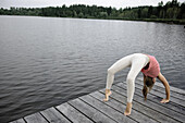 Young woman bridging on a jetty at lake Starnberg, Bavaria, Germany