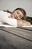 Young woman lying on a jetty, lake Starnberg, Bavaria, Germany