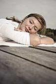 Junge Frau liegt auf einem Steg, Starnberger See, Bayern, Deutschland