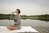Junge Frau trinkt eine Flasche Wasser, sitzt auf einem Steg am Starnberger See, Bayern, Deutschland