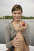 Young woman holding an apple, lake Starnberg, Bavaria, Germany
