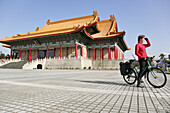 Young German woman on bicycle in front of National Theatre and National Concert Hall, Taipei, Republic of China, Taiwan, Asia