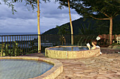 Woman reading a book in pool of hot springs, East Sun Spa Spring Hotel, Jinluan Hot Springs, Jinluan, Republic of China, Taiwan, Asia