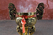 Vessel for incense sticks in front of red wall, Kuanti Temple, Tainan, Republic of China, Taiwan, Asia