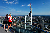 Two young women admiring the view towards the Commerzbank Tower, Frankfurt am Main, Hesse, Germany