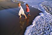 Junge und Mädchen laufen von der Wellen und Schaum der Brandung am Sandstrand weg
