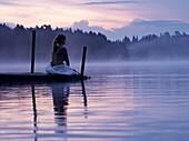 Frau sitzt morgens auf dem Steg eines See, Schweden, Europa