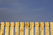 Lattenzaun und blauer Himmel im Hintergrund