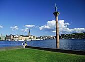 Paar in Stockholm City Hall Park am Riddarfjärden gegenüber Riddarholmen, Blick auf Gamla Stan, Altstadt, Stockholm, Schweden