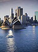 Sydney Skyline mit Opera House, Licht spiegelt sich im Dach, Sydney, New South Wales, Australien