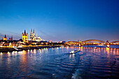 View over river Rhine to old town with cathedral and Great St. Martin church at night, Cologne, North Rhine-Westphalia, Germany