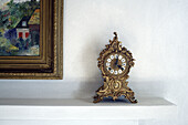 Old antique clock standing on the mantelpiece of a fire-place besides a colorful painting of the famous painter Monet,  Gabiano,  Piemont,  Italy,  Europe
