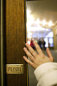Hand of a woman pushing a door open at Grand Central Terminal railway station,  Manhattan,  New York City,  United States,  North America