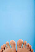 Barfuss, Barfuß, Blau, Eine Person, Eins, Erwachsene, Erwachsener, Farbe, Füsse, Fuß, Fußsohle, Fußsohlen, Konzept, Konzepte, Körper, Körperteil, Körperteile, Mensch, Menschen, Symmetrie, Symmetrisch, Zehe, Zehen, L28-724590, agefotostock