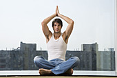 Man sitting in yoga position on floor