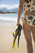 Woman holding snorkel gear on the beach  Maui,  Hawaii  Model released