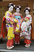 Three young Japanese tourists who have been dressed up to look like geisha,  pose infront of a Japanese gate in the Gion district of Kyoto