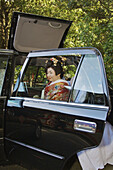 A just married Japanese bride and groom sitting in a special marriage taxi showing it´s special roof hatch opened to allow the bride with a high wedding hair style to get inside the taxi without trouble