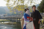 A Japanese man wearing a traditional kimono and a woman dressed up as a geisha are standing infront of the famous bridge Togetsu-kyo,  the dominant landmark in Arashiyama with autumn leaf colors in the back ground