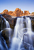 A waterfall tumbles over rocks below a jagged sandstone ridge illuminated in the last light of the day near Moab,  Utah