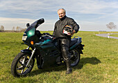 Bike, Biker, Europe, Fall, German, Germany, Grey, Helmet, Jacket, Leather, Man, Motor, Motorbike, Old, Pensioner, Pose, Relax, Rest, Retired, Road, Stop, Travel, T91-811122, agefotostock