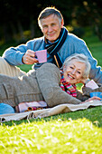 Adult, Adults, Calm, Calmness, Caucasian, Caucasians, Chill out, Chilling out, Color, Colour, Contemporary, couple, couples, Cup, Cups, Daytime, exterior, Facing camera, female, Grass, grin, grinning, happiness, happy, Hold, Holding, human, joy, Lawn, Lea