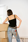 Adult, Adults, At home, back view, Blue jean, Blue jeans, Box, Boxes, Brunette, Brunettes, Cardboard, Color, Colour, Contemporary, D i y, Dark-haired, Daytime, Denim, DIY, Do it yourself, Do-it-yourself, Female, Hands on the waist, Heap, Heaped, Heaps, Ho