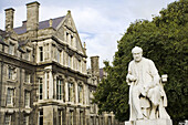 Statue of a man in front of an education building Trinity College, Dublin, Republic Of Ireland