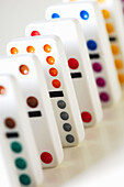 White dominos with multicolored dots stand in a line on white background