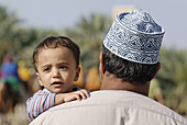 Omani father with son in traditional dress,  Nakhl,  Batinah Region,  Sultanate of Oman,  Arabia,  Middle East