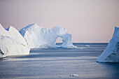 View at iceberg with hole at Ilulissat Kangerlua Isfjord at dusk, Disko bay, Kitaa, Greenland
