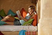 Young woman reading a book, colourful cushions, Cala Llamp [-], Andratx, Mallorca, Balearic Islands [-], Spain
