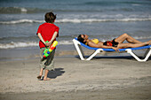 Young boy with water pistol, woman on a sun lounger, Mallorca, Balearic Islands, Spain