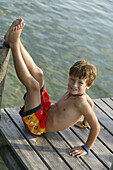 Young boy sitting on pier, Chiemsee, Bavaria, Germany