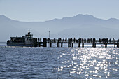 Ferryboat at the main pier, Kampenwand Mountain in the background, Fraueninsel, Lake Chiemsee, Chiemgau, Bavaria, Germany