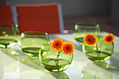 Green glass bowls with orange gerbera flowers