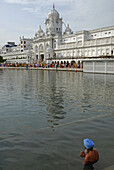 Man with turban bathing in water basin in front of the Golden Temple, view at main entrance, Sikh holy place, Amritsar, Punjab, India, Asia