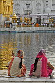 Two women in front of the Golden Temple, woman taking pictures with cell phone, Sikh holy place, Amritsar, Punjab, India, Asia