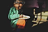 Girl eating in kitchen at Makaibari tea plantation, Darjeeling, West Bengal, India, Asia