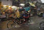 Downpour in Paharganj, Mainbazar, cycle rickshaw in the floods, New Delhi, Indian capital, India, Asia