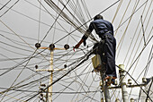 Electrician in a ravel of wires in dowtown Hyderabad, Andhra Pradesh, India, Asia