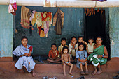 Family and other kids from the village in front of house in Mali village, Tribal region in Koraput district in southern Orissa, India, Asia