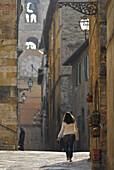 Frau in einer Gasse in der Altstadt mit Blick auf den Kirchturm, Colle di Val d' Elsa, Toskana, Italien, Europa